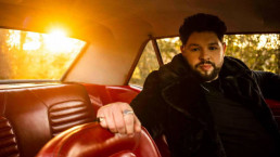 Eurovision singer James Newman poses in a car